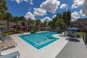 Pool area with sun chairs and patio tables with umbrellas
